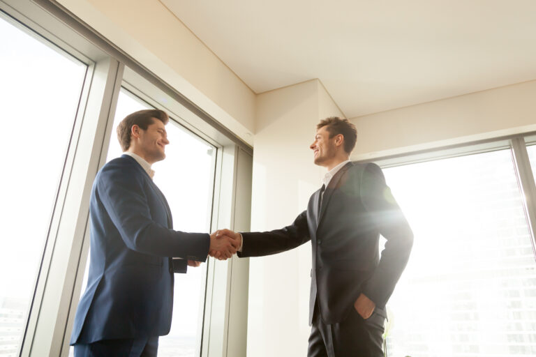 Smiling executive director handshaking with business partner in office, thanking company manager for good work, congratulating employee with promotion. Successful negotiation, strong partnership