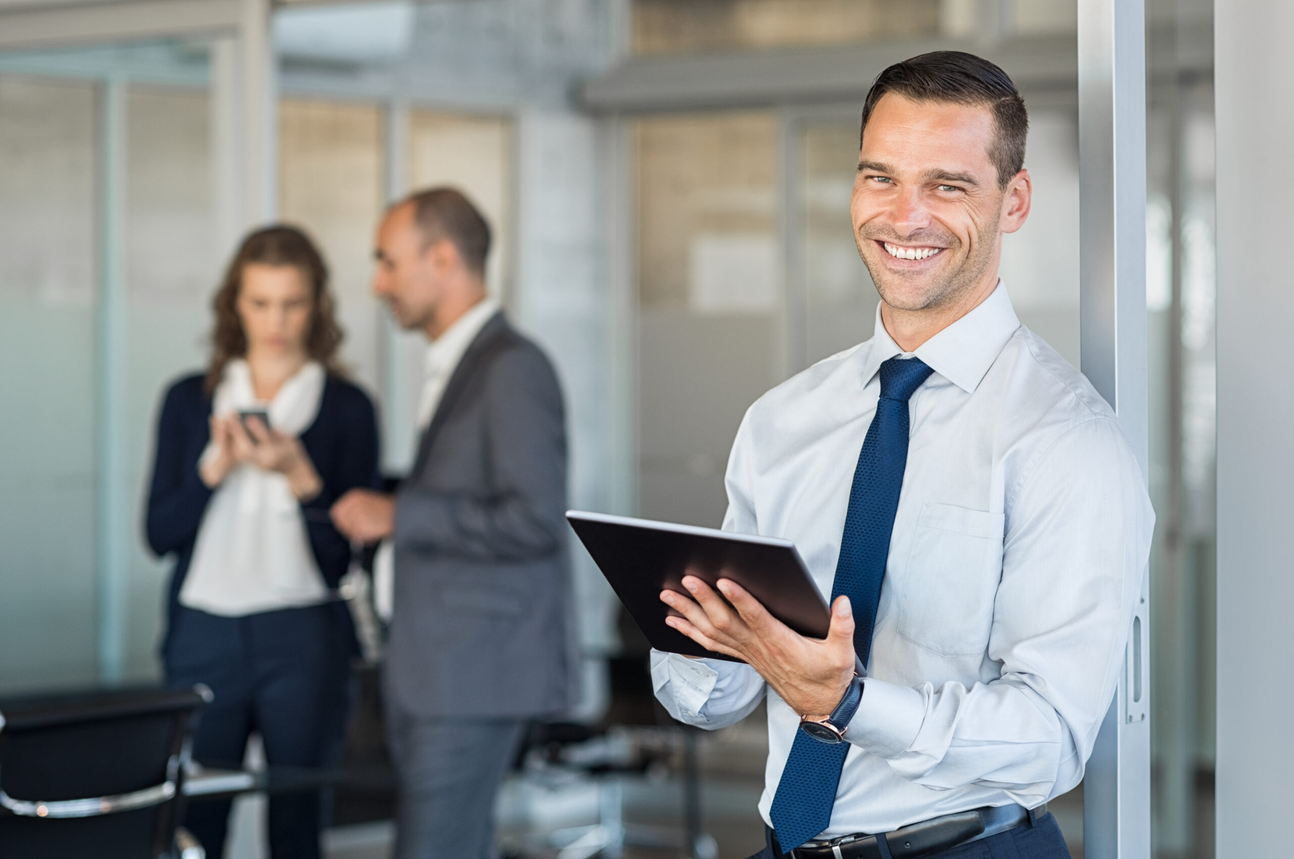 Happy,Businessman,Holding,Digital,Tablet,With,Team,Discussing,Project,In