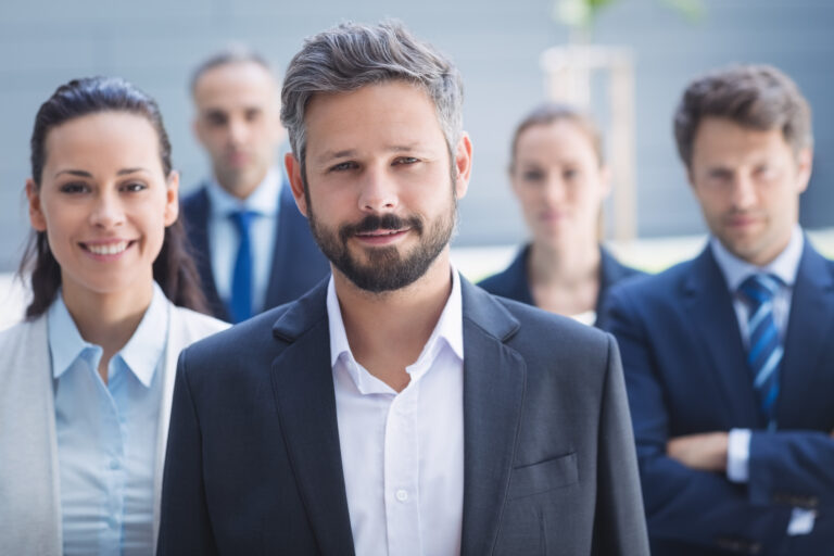 Portrait of confident businessman with colleagues standing outside office building