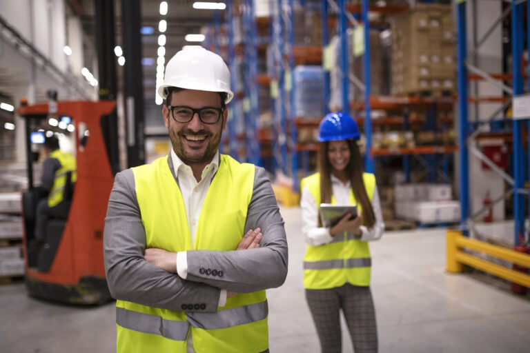 Portrait of successful warehouse worker or supervisor with crossed arms standing in large storage distribution area.